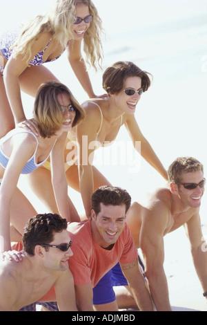 Groupe de jeunes formant une pyramide humaine sur la plage Banque D'Images