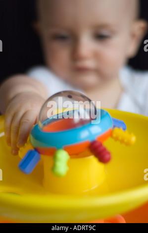 Un bébé de 9 mois garçon tenant son jouet Banque D'Images