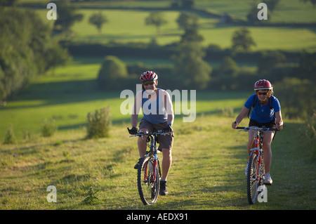Homme Femme en vtt vélo sur Hambledon colline au-dessus de la vallée de Blackmore Dorset England UK Banque D'Images