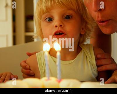 Little girl blowing out deux bougies allumées sur son deuxième anniversaire de son nom est Irene Banque D'Images