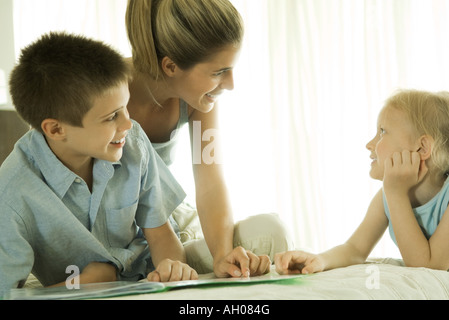 Mère d'aider les enfants à faire leurs devoirs Banque D'Images