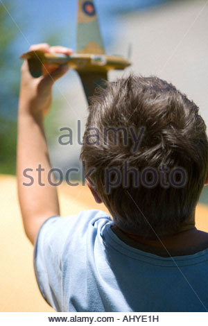 Boy Playing with toy 810 aero avion en jardin d'été close up vue arrière Banque D'Images