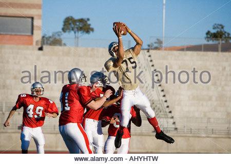 Joueurs de football américain opposant pour balle au cours de jeu compétitif, receveur offensif attraper la balle Banque D'Images