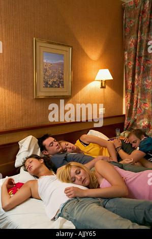 Les amis endormis on hotel bed Banque D'Images