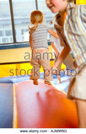 Deux garçons et une fille en lecture sur un château gonflable gonflable Banque D'Images