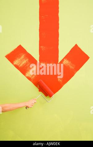 Main de femme de race blanche rouge peinture vers le bas la flèche sur le mur Banque D'Images