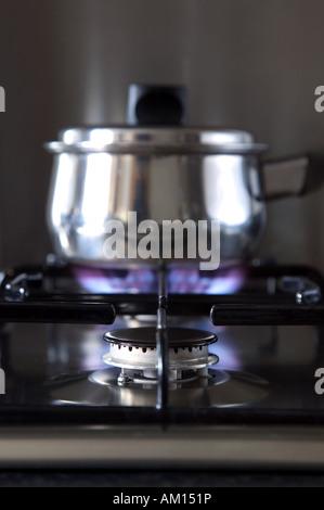 Gros plan d'une cuisinière à gaz avec une casserole sur le brûleur arrière DOF peu profondes Banque D'Images