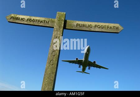 Un avion de ligne arrive en terre à l'aéroport de Londres Gatwick, sur un signe de diriger pour randonneurs sur Banque D'Images