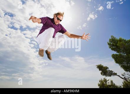L'homme portant des lunettes de sauter dans l'air. Banque D'Images