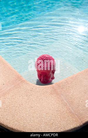 En regardant une tête de bouddha rose de soleil sur coin étapes d'une piscine privée Banque D'Images