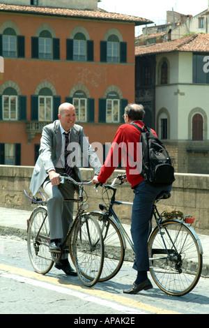 Deux cyclistes de parler face à face les banlieusards se rencontrent autour d'un chat Florence Toscane Italie Banque D'Images