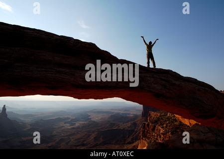 La célébration de l'homme sur le haut de Mesa Arch, Canyonlands National Park, Utah, USA Banque D'Images