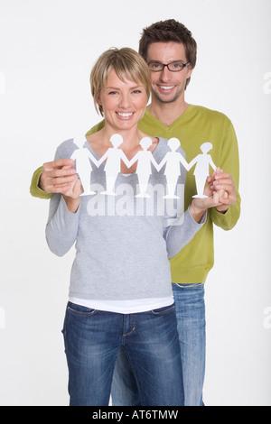 Young couple holding papier découpé, portrait Banque D'Images