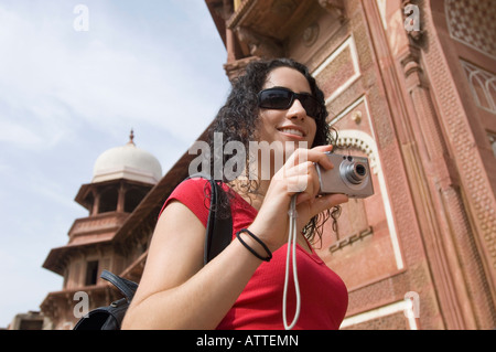 Low angle view of a young woman holding a digital camera and smiling, Taj Mahal, Agra, Uttar Pradesh, Inde Banque D'Images