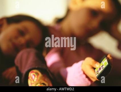 Jeune garçon s'appuyant sur l'épaule de jeune fille regardant la TV, Close up, blurred Banque D'Images