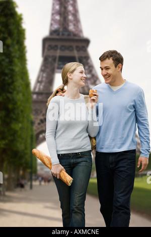 Couple en train de marcher avec la Tour Eiffel en arrière-plan Banque D'Images