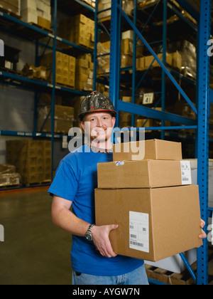 Warehouse worker holding pile de boîtes Banque D'Images
