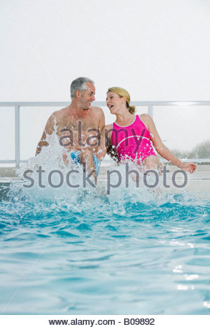 Senior couple sitting on edge of swimming pool rire et projections Banque D'Images