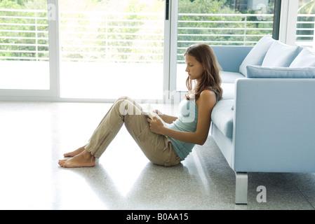 Teenage girl sitting sur le sol, appuyé contre un canapé, livre de lecture, side view Banque D'Images