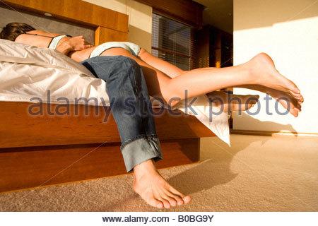 Jeune femme se trouvant au sommet de l'homme sur le lit Banque D'Images
