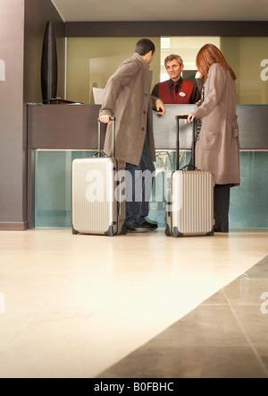 Couple dans l''hôtel parle à Concierge Banque D'Images