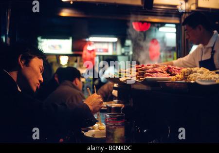 L'homme de manger à l'un des peu de lumière servant à Shinjuku Izakayas Yakitori's Golden Gai domaine dans la capitale Banque D'Images
