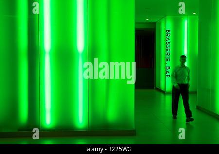L'homme marche sur le vert néon lumineux hall de l'hôtel Cumberland, Londres, Angleterre Banque D'Images