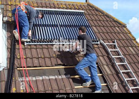 Deux ingénieurs de poser les panneaux de chauffage solaire pour chauffer l'eau domestique sur un toit d'une propriété Banque D'Images