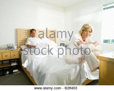Portrait de femme sur le bord du lit en pyjama par man using laptop computer in bed Banque D'Images