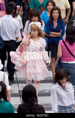 Une fille habillé en lolita frous-style fashion est de marcher dans la foule traversant une rue de Tokyo occupé Banque D'Images