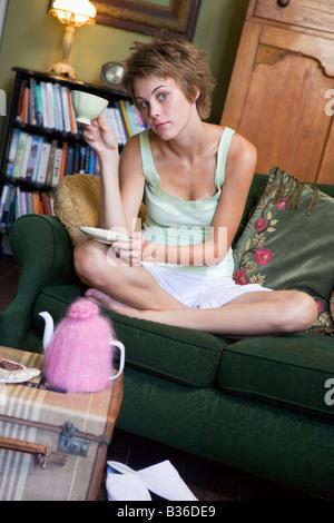 Jeune femme assise sur le canapé à la maison boire du thé Banque D'Images
