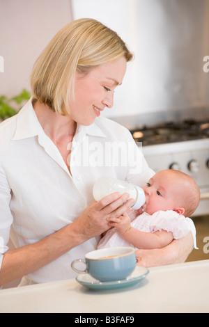 Mère de nourrir bébé dans la cuisine avec cafetière smiling Banque D'Images