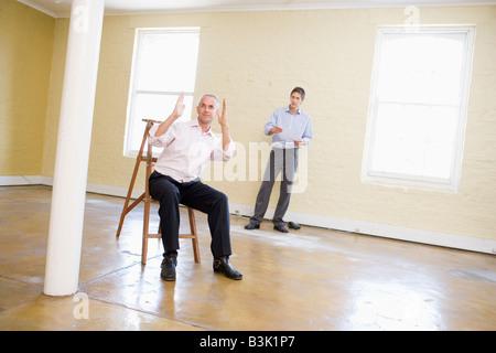 Deux hommes avec échelle dans l'espace vide de faire des plans pour prix Banque D'Images