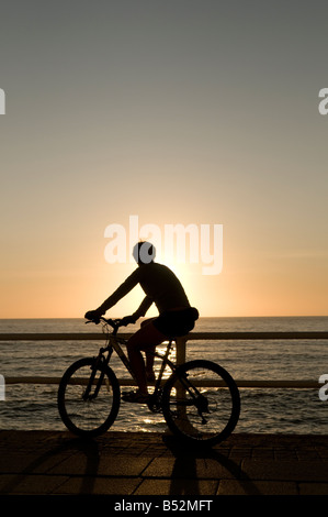Silhouette de jeune femme fille en bicyclette à la recherche au coucher du soleil le long de la promenade de front Banque D'Images