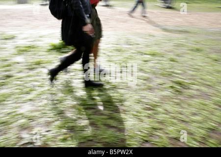 Deux personnes marchant sur le chemin boueux in rural field Banque D'Images