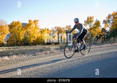 Les cyclistes masculins en descendant une route rurale en gravier près de Salida, Colorado, USA Banque D'Images
