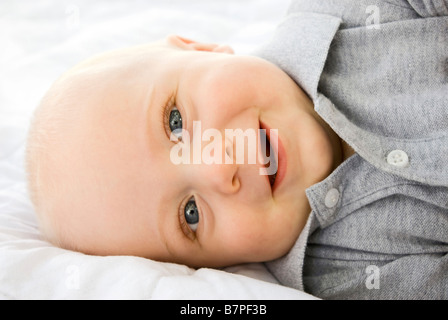 Baby lying on blanket smiling Banque D'Images