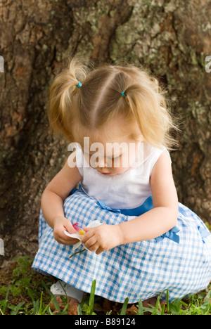Petite fille jouant à côté de tree Banque D'Images