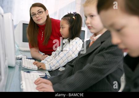 L'observation de l'enseignant à l'aide d'ordinateurs pour enfants Banque D'Images