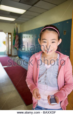 Girl listening to mp3 player in school hallway Banque D'Images