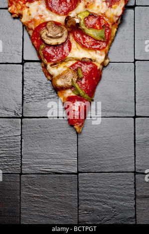 Une tranche de pizza sur un fond en bois noir Banque D'Images