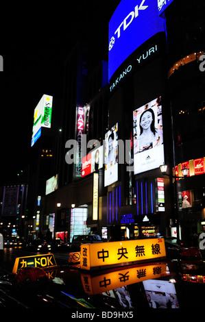 Taxi sign avec des écrans publicitaires en arrière-plan dans Ginza Tokyo Japon Banque D'Images