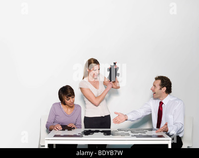 Un trio d'affaires faire un puzzle denteux Banque D'Images
