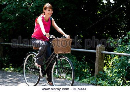 Une jeune femme en vélo le long d'une route de campagne Banque D'Images