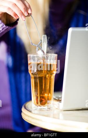 Jeune femme assise dans un café avec une tasse de thé, à l'aide d'un ordinateur portable, la Suède. Banque D'Images