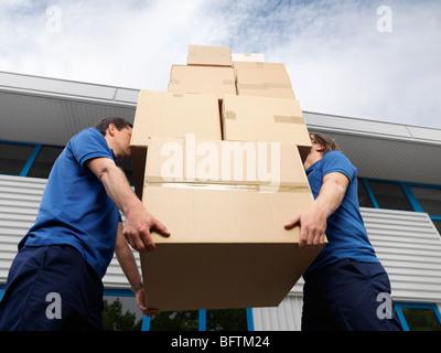Deux hommes chargés de boîtes Banque D'Images