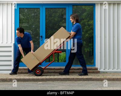 Deux hommes chargés de boîtes sur chariot Banque D'Images