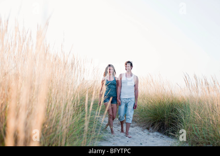 Couple strolling along beach Banque D'Images