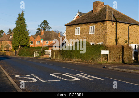 Le marquage routier lente sur un village rural country road, Seer Green Buckinghamshire, Royaume-Uni Banque D'Images