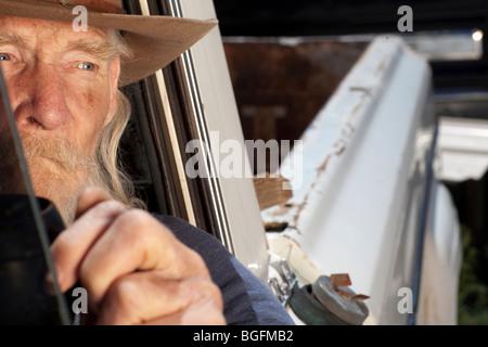 Un vieil homme avec une barbe blanche au volant d'une camionnette et regardant par la fenêtre Banque D'Images